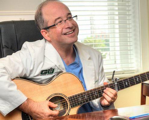 Dr. Scott Miller holding a guitar
